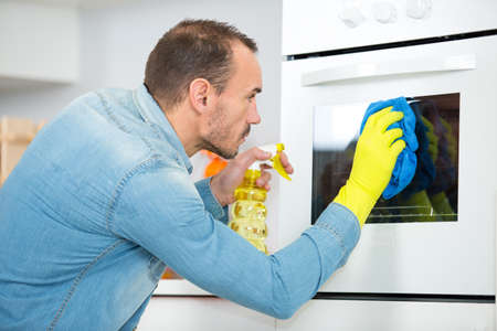 man cleaning oven in domestic kitchen Фото со стока