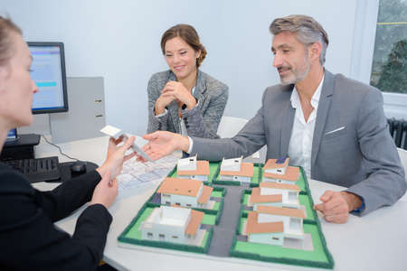 couple with real-estate agent discussing project