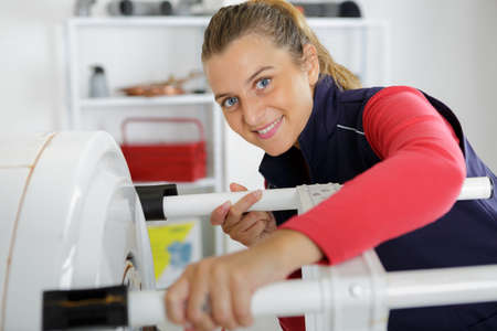 female technician servicing a boiler using tablet computer