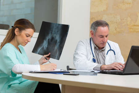 portrait of doctors with xray report in hospital