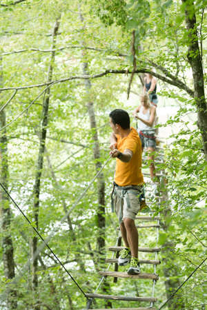 adults crossing rope bridge suspended between trees