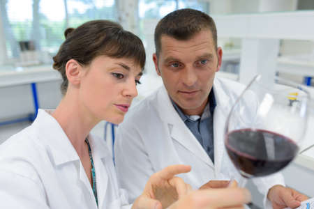 man and woman experts in white coats checking wine quality