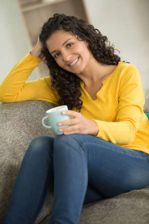 Happy woman drinking coffee on a sofa at home Stock Photo