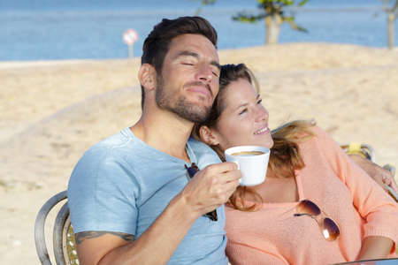 couple relaxing with a coffee in cafe by the beach 版權商用圖片