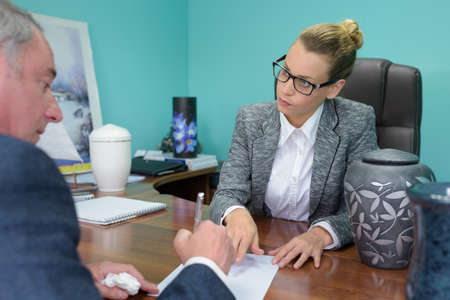 boss giving a document to a sad employee in office