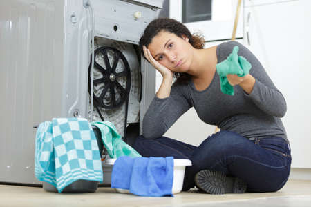 troubled woman looking at leaking at machine in kitchen