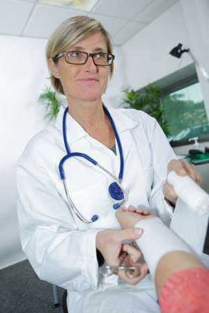 female doctor bandaging male hand sprained wrist