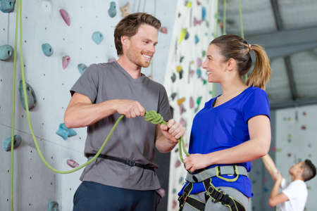 instructor securing a climbers rope by indoor wall