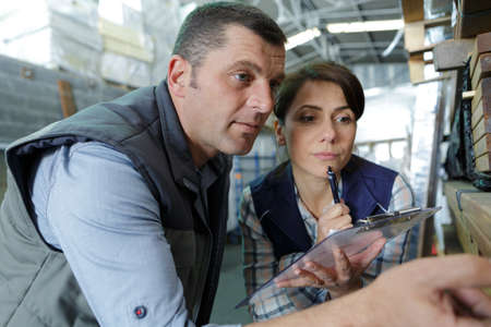 man and woman in warehouse discussing over tablet 스톡 콘텐츠