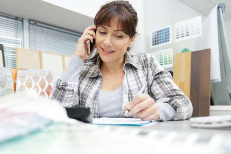 woman talking on mobile phone in office Фото со стока