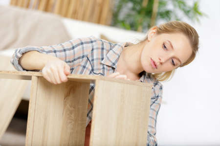 a woman assembling furniture alone Stockfoto