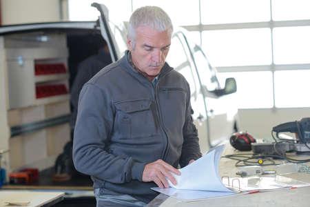 man looking through folder in workshop van in background Reklamní fotografie - 150550594