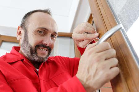 locksmith man try to fix knob on wood door