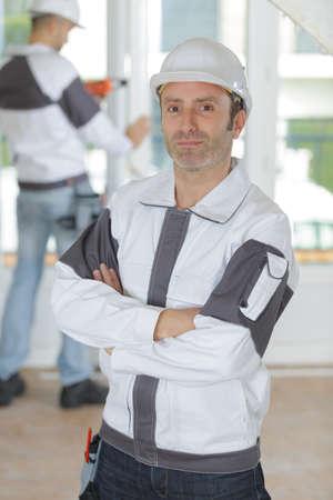 happy man builder in helmet standing with arms crossed