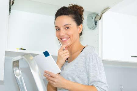 portrait of woman installing kitchen cupboard Stockfoto