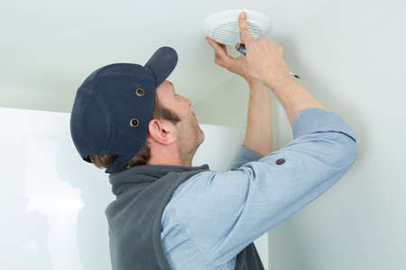 young man changing a led bulb at house