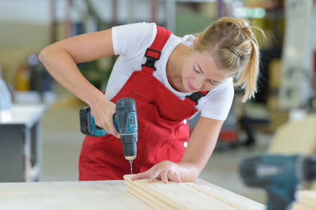 female carpenter drilling on wood Reklamní fotografie