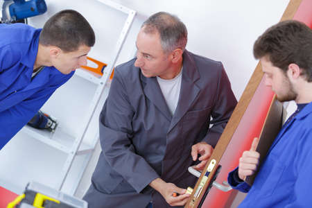 young men learning to fix the door with screwdriver