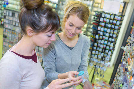 Women in craft shop looking at buttons