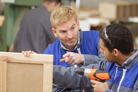 woodworking trainer supervising his apprentice Imagens