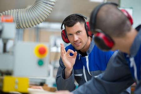 handsome carpenter wearing earmuff showing ok sign in workshop Reklamní fotografie