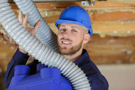 builder working on ventilation pipes Stok Fotoğraf