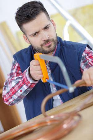a plumber cutting copper tube