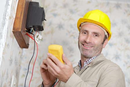a happy builder measuring voltage Stockfoto