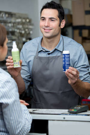 man with apron holding showing spray to customer