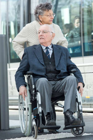 elderly man seated in wheelchair pushed by his wife