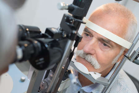 elderly man with presbyopia at the optician for optical examination