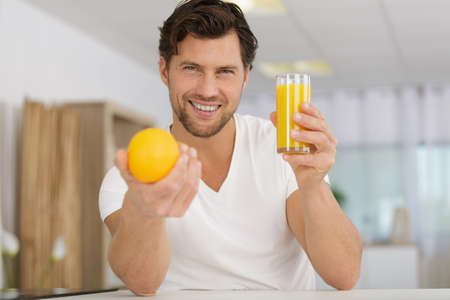 man holding a glass of orange juice and a fruit