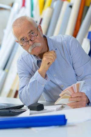 senior man doing work in his studio Imagens