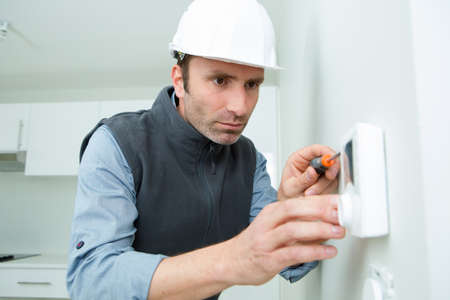 worker fixing thermostat in building