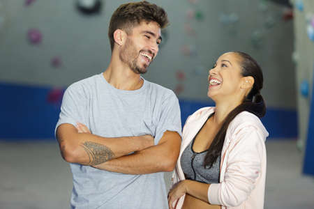 happy man and woman at indoor climbing gym wall