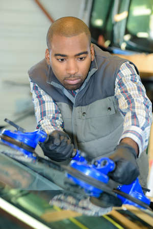 portrait of man fitting new windshield Stock Photo