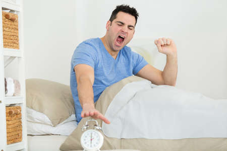 yawning man sitting up in bed to turn off alarm-clock Banque d'images