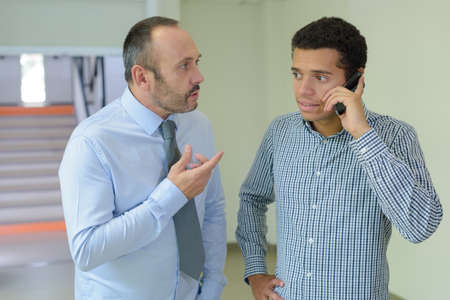mid-adult businessman and colleague talking on phone in office