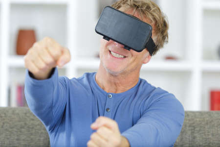 mature man in virtual reality glasses drives an invisible car