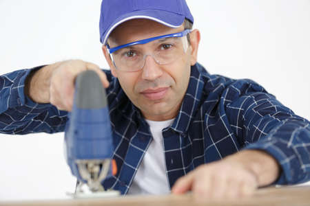 portrait of mature man using jigsaw tool Banque d'images