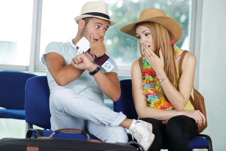 portrait of agitated young couple waiting for a plane