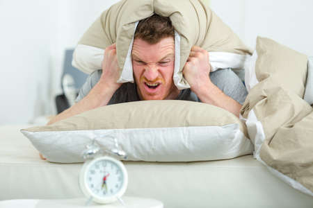 man covering his head with a pillow