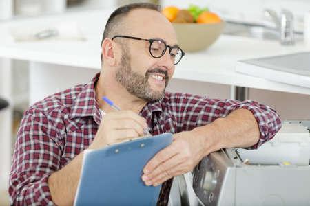 happy man with clipboard near washing machine
