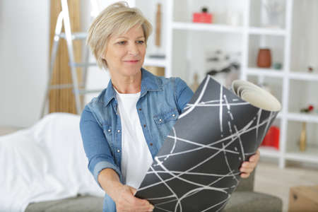 mature woman considering roll of wallpaper