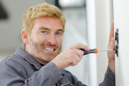 electrician with a screwdriver during the installation