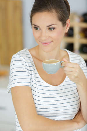 serene smiling woman holding small cup of coffee
