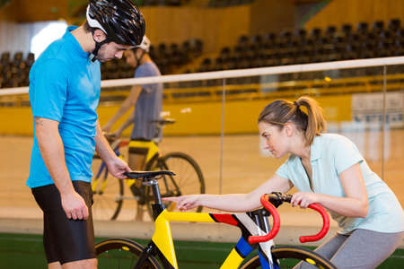 coach inspecting seat on bicycle in velodrome Banque d'images