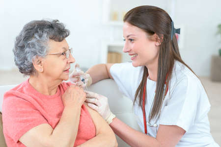 nurse giving injection to senior woman in the arm