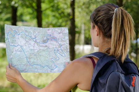 rear view of woman in the countryside looking at map