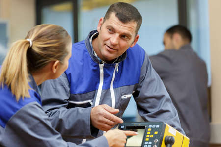 technicians in discussion by electronic equipment